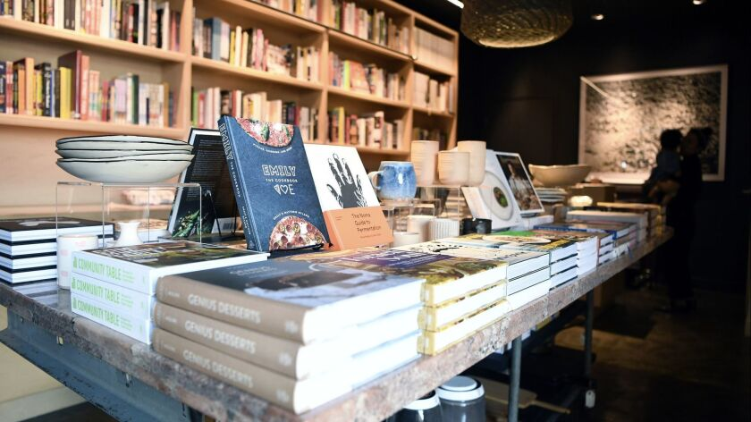 At Now Serving, shelves of cookbooks and a center island of ceramics and more cookbooks.