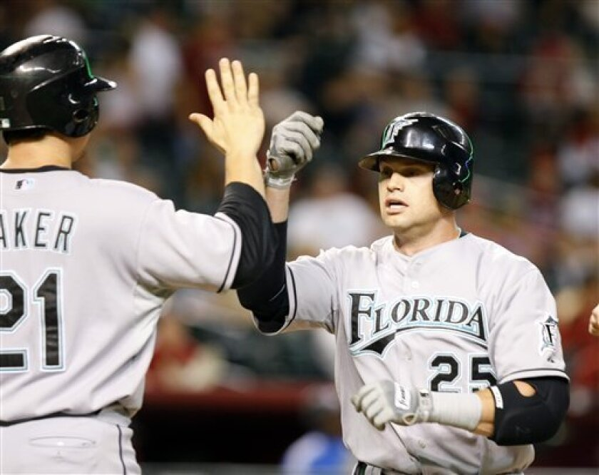 Florida Marlins' Brett Carroll, right, is congratulated by John Baker, after hitting a three-run pinch-hit home run in the eighth inning against the Arizona Diamondbacks' in the first inning during a baseball game on Thursday, July 9, 2009, in Phoenix. (AP Photo/Rick Scuteri)