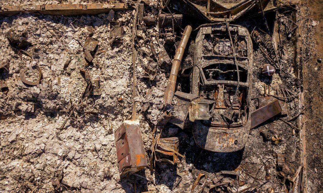 An aerial picture taken on September 24, 2021 a burned vehicle sits parked at a burned home in Greenville, California.