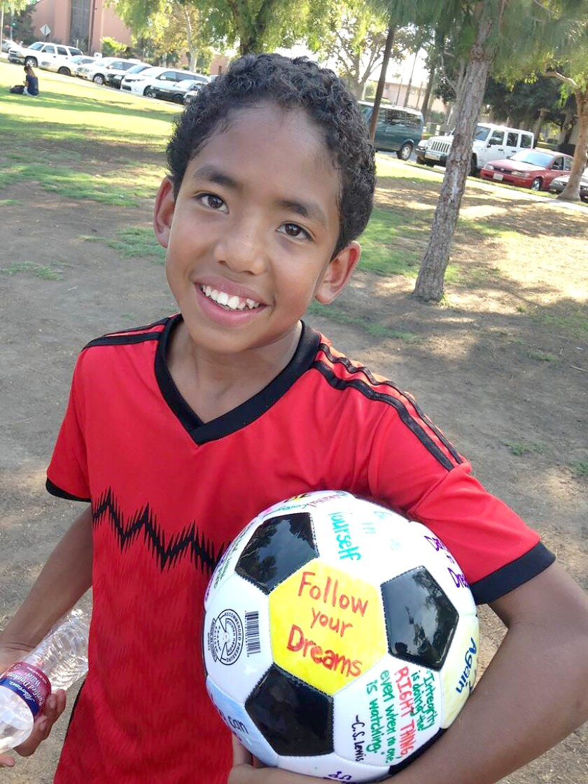 A kid in the Pure Game program holds a soccer ball. Pure Game uses soccer to mentor kids, teaching them character.