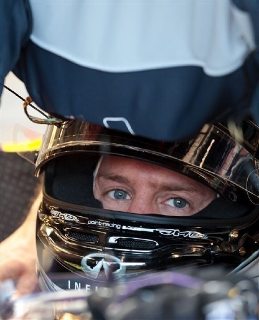 Red Bull driver Sebastian Vettel of Germany sits in the cockpit of his car during the first practice session for Sunday's Australian Formula One Grand Prix at Albert Park in Melbourne, Australia, Friday, March Friday, 2013. (AP Photo/John Donegan)