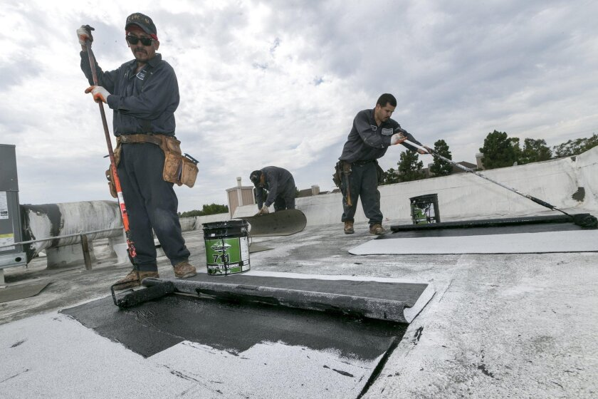 Roofers Javier Rubio, left, and Joel Camberos with Hull Brothers Roofing & Waterproofing resurface roofs at the Marina del Rey seaside community of Los Angeles on Tuesday, Aug. 25, 2015. While drought-plagued California is eager for rain, the forecast of a severe El Niño event has communities clear