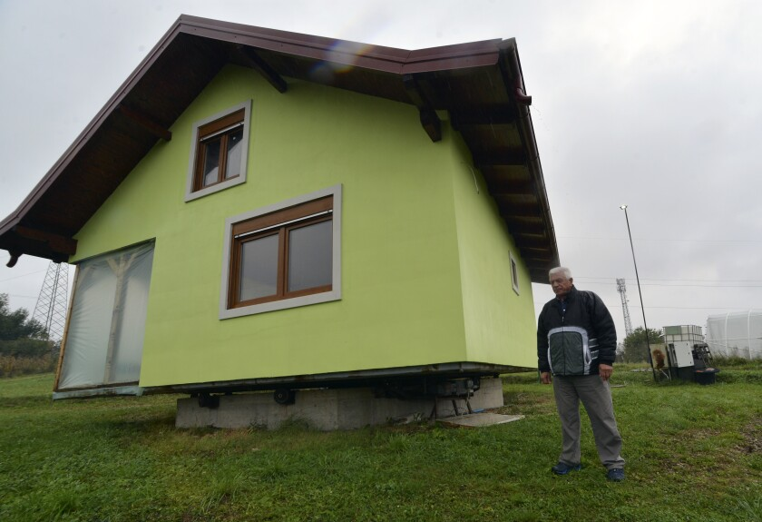 Vojin Kusic's stands in front of his rotating house in a town of Srbac, northern Bosnia, Sunday, Oct. 10, 2021. The house designed and built by 72-year-old Vojin Kusic, with its green façade and red metal roof, can rotate a full circle to satisfy his wife's shifting desires as to what she should see when she looks out of the windows of her home. (AP Photo/Radivoje Pavicic)