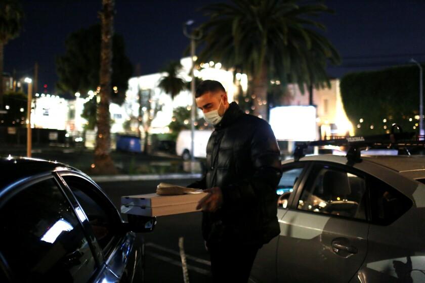 Luca Zafferano serves a customer their order at L'Antica Pizzaria da Michele in Hollywood.