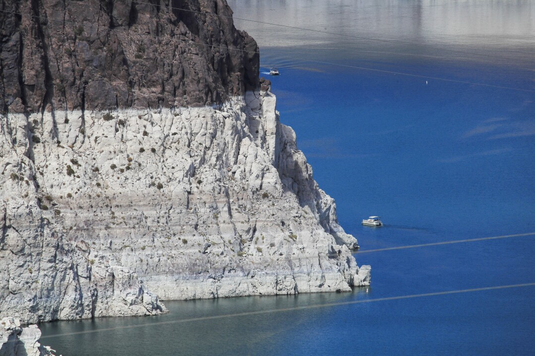 A boater gets an up-close view of previously submerged surfaces at Lake Mead.