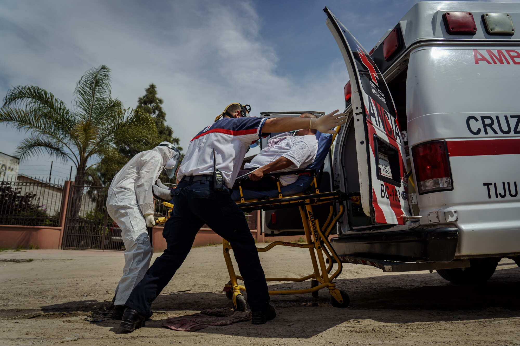 Sergio Garcia swings the ambulance door wide open as Red Cross paramedics help transport Eduardo Dionisio Molina, 41, who has symptoms related to COVID-19, to a nearby hospital from his home in the Ejido Matamoros neighborhood of Tijuana, Mexico, on April 29, 2020.