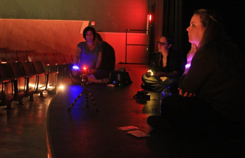 From the stage of the darkened Avo Theater in Vista members of the San Diego Paranormal Research Society, from left, Donna Malmborg, Delia Rugamas and Nicole Strickland attempt to communicate with paranormal energies Saturday night. photo by Bill Wechter