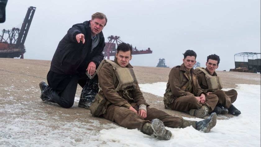 """From left, director Christopher Nolan with Harry Styles, Aneurin Barnard and Fionn Whitehead during the filming of the Warner Bros. action thriller """"Dunkirk."""""""