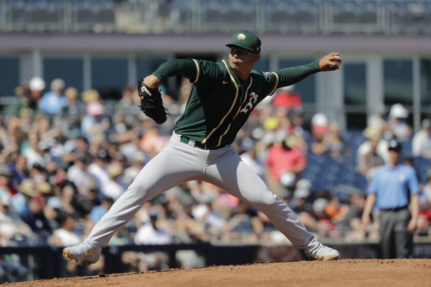FILE - In this May 7, 2020, file photo, Oakland Athletics starting pitcher Jesus Luzardo throws against the Seattle Mariners during a spring training baseball game in Peoria, Ariz. Luzardo broke into the majors in September, striking out 16 in 12 innings and recording two saves in six relief appearances. But the A's think his future is in their rotation. (AP Photo/Elaine Thompson, File)