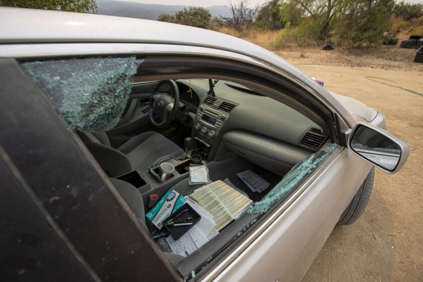 The broken passenger window of a car on the property.
