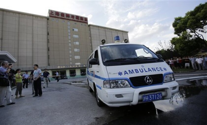 An ambulance leaves the plant of Weng's Cold Storage Industrial Co. Ltd. on the outskirts of Shanghai, China, Saturday, Aug. 31, 2013. At least 15 people were killed Saturday after liquid ammonia leaked from a refrigeration unit at the cold storage plant in Shanghai, state media and the government