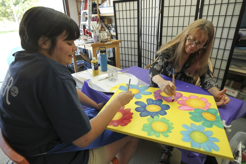 """Katie Flores, 24, left, who has autism and local artist Moya Devine work together on a painting titled """"Groovy Flowers"""" which will be part of the Radical Inclusion traveling art exhibition, while in the garage of Devine's Encinitas home on Thursday."""