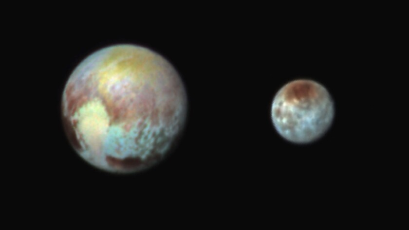 This false-color image of Pluto, left, and Charon highlights the differences in surface material and features of the two bodies. New Horizons captured this image on the day before its historic flyby.