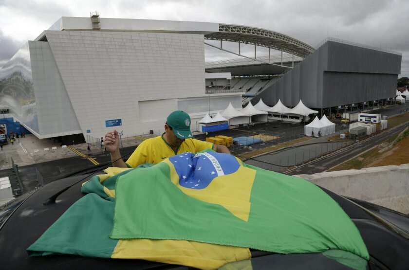 A Brazilian fan tries to tie his country's flag on top of his car, outside Arena de Sao Paulo, Brazil, on Tuesday, June 10, 2014. The World Cup is set to open on June 12 with Brazil facing Croatia in Sao Paulo. (AP Photo/Thanassis Stavrakis)