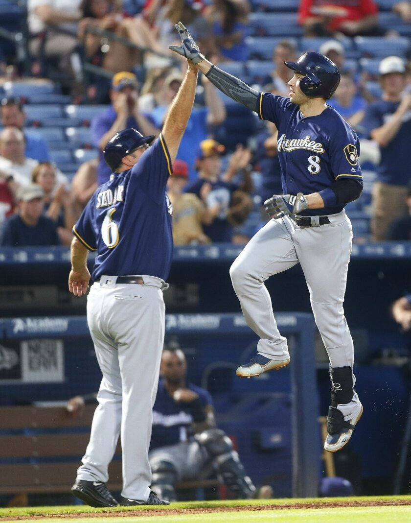 Milwaukee Brewers' Ryan Braun (8) celebrates with third base coach Ed Sedar (6) as he runs the bases after hitting a solo home run during the fifth inning of a baseball game against the Atlanta Braves on Thursday, May 26, 2016, in Atlanta. (AP Photo/John Bazemore)