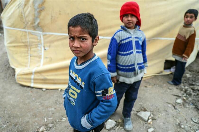 Niños desplazados sirios posan en un refugio en al-Asha'ari, al este de al-Ghouta (Siria). EFE/Archivo