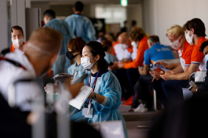 Members of the Netherlands delegation wait for screening and COVID-19 testing upon their arrival on a flight to Tokyo.