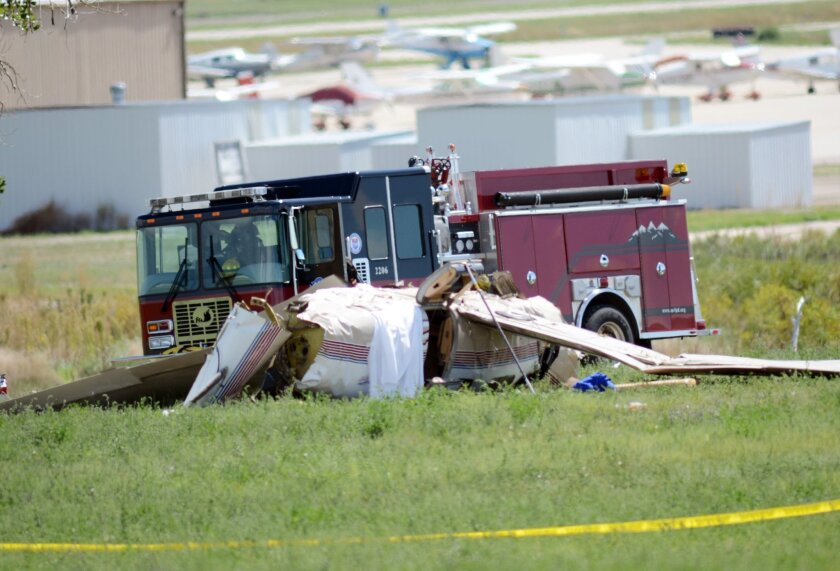 Firefighters work on the scene where three people were killed and two others injured after an airplane crashed in a field northwest of the main runway at Erie Municipal Airport while coming in for a landing in Erie, Colo., Sunday, Aug. 31, 2014. (AP Photo/The Daily Camera, Cliff Grassmick)