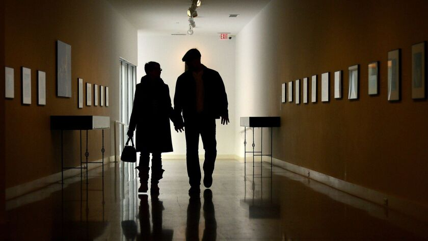 FILE - In this Jan. 7, 2014, file photo, a couple walks down the Bacon Gallery at the Erie Art Museu