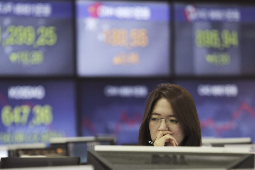 A currency trader watches monitors at the foreign exchange dealing room of the KEB Hana Bank headquarters in Seoul, South Korea on Jan. 8, 2020. Shares were mostly higher in Asia on Monday, Aug. 10, 2020 after President Donald Trump issued executive orders to provide tax relief and stopgap unemployment benefits for Americans hit by the fallout from the coronavirus pandemic. (AP Photo/Ahn Young-joon)