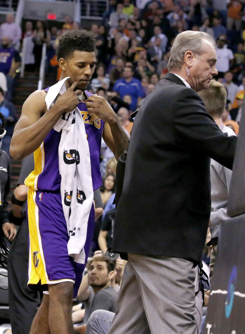 Lakers small forward Nick Young is escorted from the court after being involved in a scuffle during the first half of Wednesday's game against the Phoenix Suns.