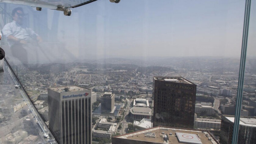 A member of the media takes a four-second ride on the Skyslide, 1,000 feet above downtown Los Angeles at the U.S. Bank Tower.