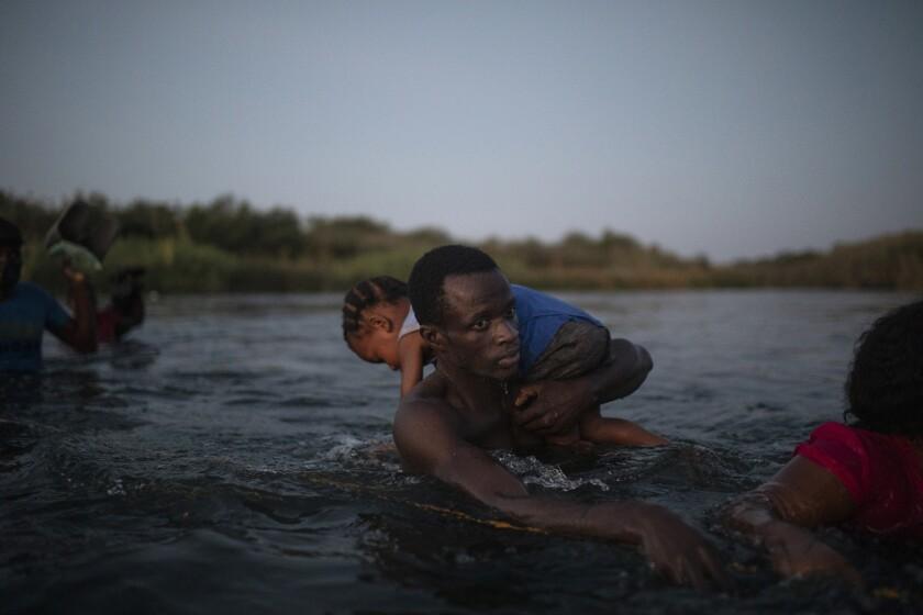 Migrants wade across the Rio Grande from Del Rio, Texas, to Ciudad Acuña, Mexico, Sunday, Sept. 19, 2021. (AP Photo/Felix Marquez)