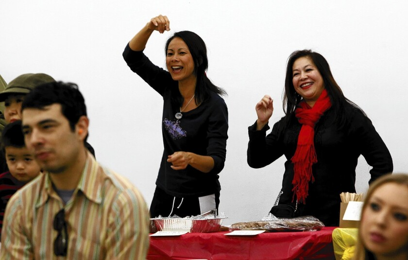 Behind a table of baked goods for sale, Christina Souza Ma, left, and Mamie Hong Weinberg dance to The Baja Bugs. The concert raised money for Castelar Elementary School's music program.