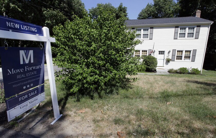 In this July 9, 2018, photo a for sale sign stands outside a pre-existing home in Walpole, Mass. On Thursday, Aug. 9, Freddie Mac reports on the week's average U.S. mortgage rates.