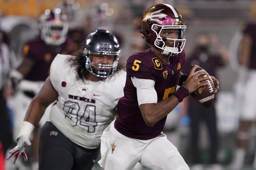 Arizona State quarterback Jayden Daniels (5) looks to throw as UNLV defensive lineman Kolo Uasike (94) pursues during the first half of an NCAA college football game, Saturday, Sept. 11, 2021, in Tempe, Ariz. (AP Photo/Matt York)