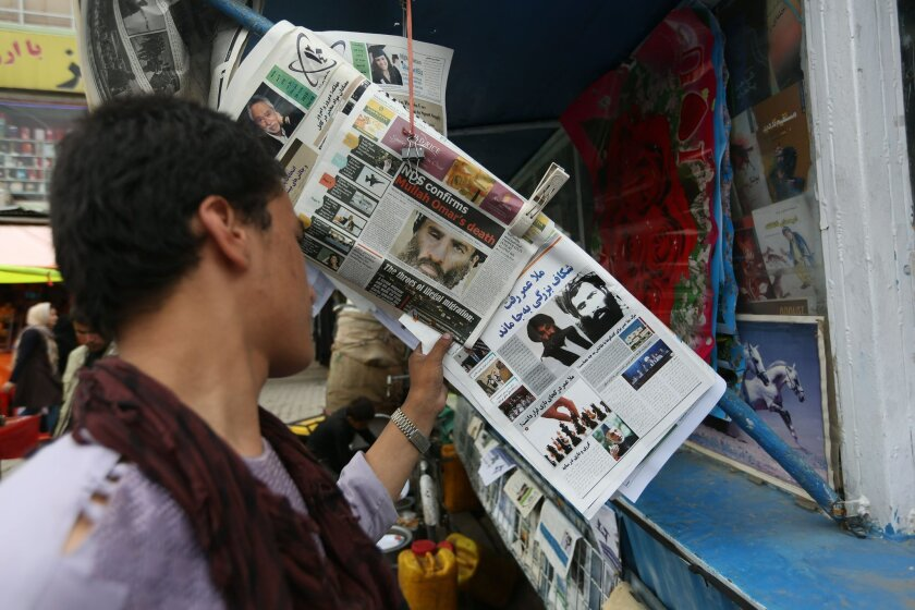 FILE - In this Aug. 1, 2015 file photo, an Afghan reads local newspapers carrying headlines about the new leader of the Afghan Taliban, Mullah Akhtar Mansoor, and former leader Mullah Mohammad Omar who was declared dead, on display at a newsstand in Kabul, Afghanistan. Defying the fury of Afghanistan's government and warnings from Washington, Pakistani authorities appear to be turning a blind eye to a meeting of hundreds of Taliban followers in Quetta, Pakistan, near the Afghan border, aimed at resolving a dispute over the group's leadership following the announcement of the death of one-eyed figurehead Mullah Mohammad Omar. (AP Photo/Rahmat Gul, File)