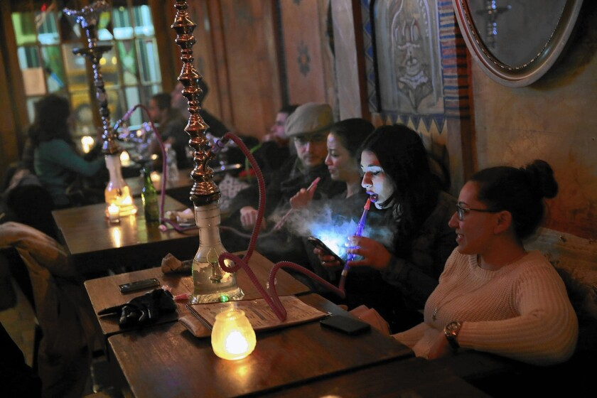 Nashwa Yosry, 20, looks at her cellphone as she smokes a hookah pipe at Sahara East in New York. It's one of 13 hookah bars targeted for closure after health inspectors found tobacco in the pipes.