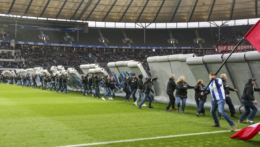 Fans tear down a symbolic wall on the day of the 30th anniversary of the fall of the Berlin Wall prior the Bundesliga soccer match between Hertha BSC Berlin and RB Leipzig at the stadium in Berlin, Germany, Saturday, Nov. 9, 2019. (Andreas Gora/dpa via AP)