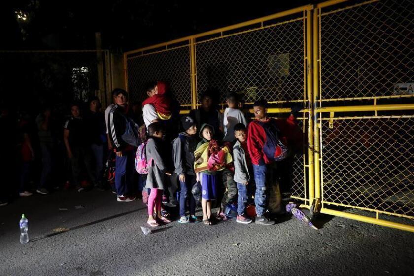 Migrantes centroamericanos, parte de la caravana de migrantes con destino hacia los Estados Unidos, esperan este sábado en la entrada de la frontera entre Guatemala y México, en Tecún Umán (Guatemala). EFE