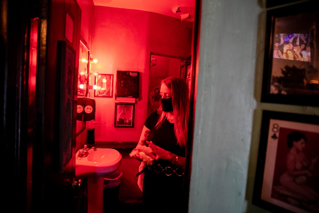 Christina Hankins, a bartender at The Tower Bar, cleans a mask in the bathroom.