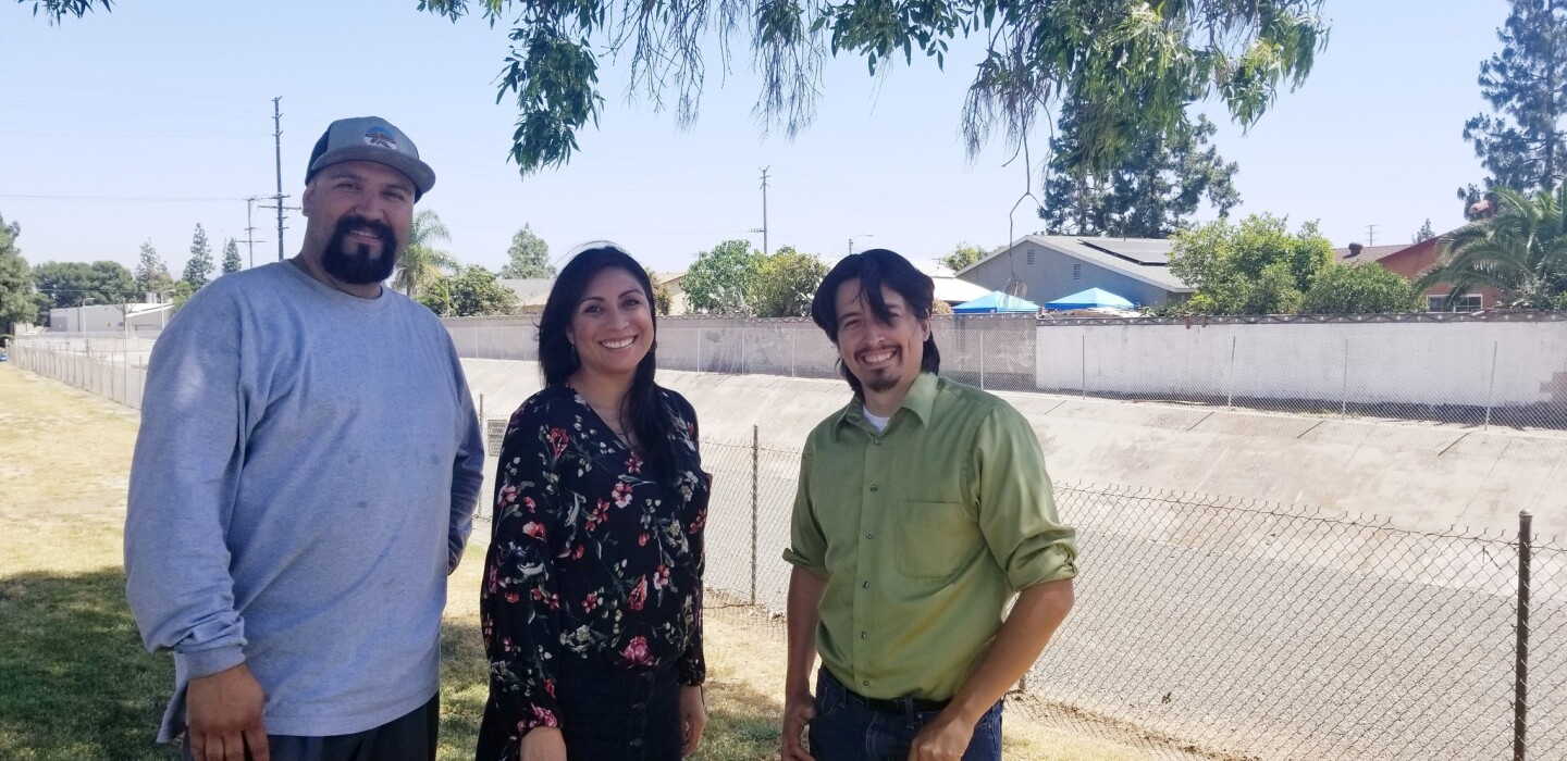 From left, Joe Parra, Xóchitl Zuniga and Joshua Correa stand in front of Manuel Hernandez-Trujillo's faded mural in the Atwood barrio of Placentia that's been there since 1977. After some trials and tribulations, they successfully got permission from the city and county to restore it.