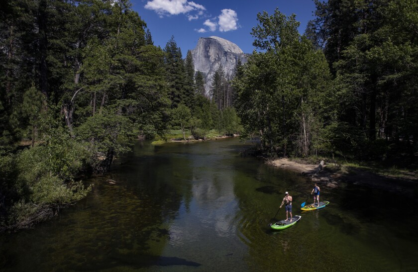 Paddleboarders on the Merced River in Yosemite, which has reopened after an 83-day shutdown.