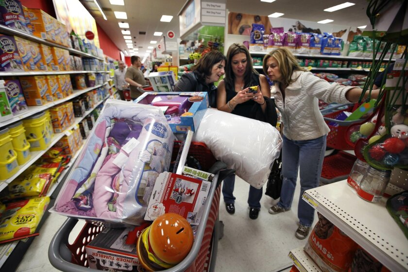 FILE - In this Nov. 28, 2014 file photo, Target shoppers Kelly Foley, left, Debbie Winslow, center, and Ann Rich use a smartphone to look at a competitor's prices while shopping  shortly after midnight on Black Friday in South Portland, Maine. After a freezing winter put a cold stop to buying and s