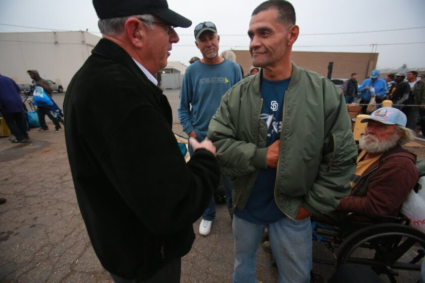 Phil Landis, left, CEO and Director of VVSD, greets Ray Urbina, a Navy veteran, and the hundred plus