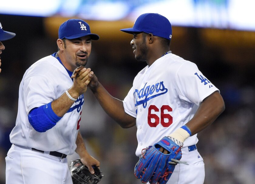 Los Angeles Dodgers' Adrian Gonzalez, left, and Yasiel Puig congratulate each other after the Dodgers defeated the Philadelphia Phillies 6-0 in a baseball game, Thursday, July 9, 2015, in Los Angeles. Both hit home runs in the game. (AP Photo/Mark J. Terrill)