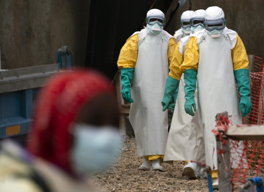 Health workers dressed in protective gear begin their shift at an Ebola treatment center in Beni, Democratic Republic of Congo, in July.