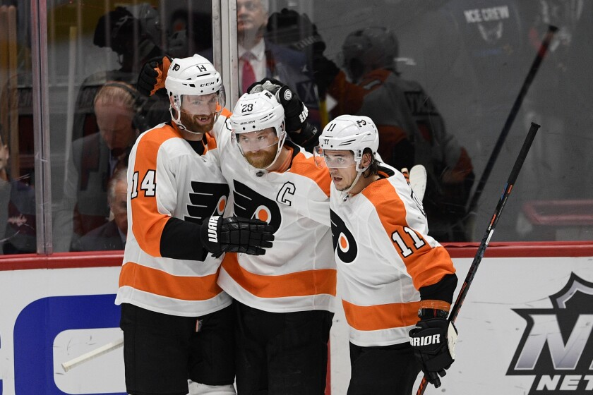 Philadelphia Flyers center Sean Couturier (14) celebrates his goal with center Claude Giroux (28) and right wing Travis Konecny (11) during the first period of an NHL hockey game against the Washington Capitals, Saturday, Feb. 8, 2020, in Washington. (AP Photo/Nick Wass)