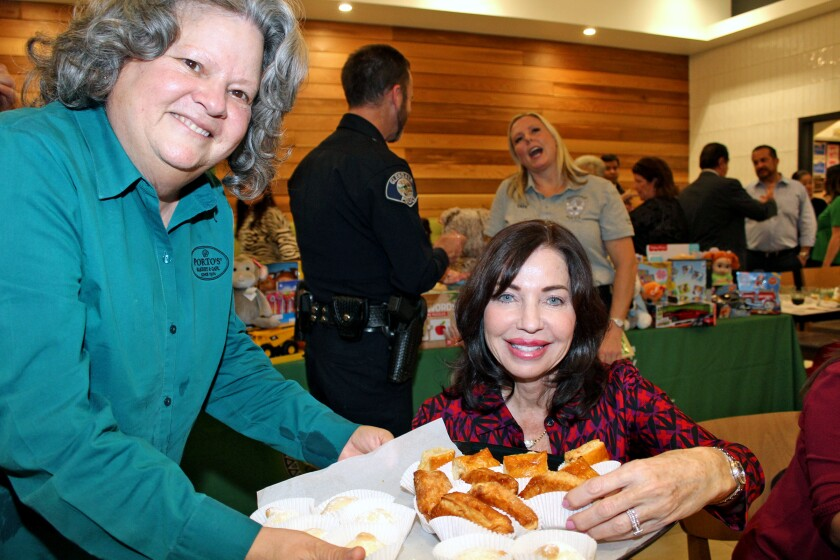 Porto's co-owner Betty Porto serves Cuban sweets to Pamela Spiszman at the Glendale Latino Assn.'s toy drive mixer.