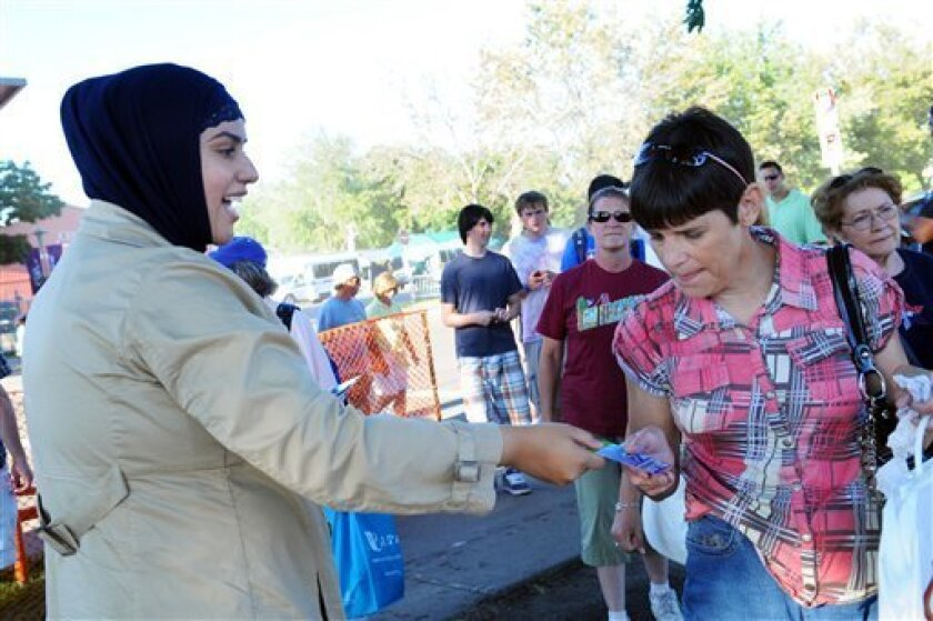 "In this Sept. 1, 2010 photo, Zuleyha Ozonder, left, hands out cards explaining Islam to fair-goers as they exit of the Minnesota State Fairgrounds in Falcon Heights, Minn. ""You just want people to take the card, spend a minute reading it and say, 'Oh. They're not terrorists,'"" said 27-year-old Zuleyha who volunteered with her husband Salim for The Islamic Circle of North America's Minnesota chapter's outreach effort. (AP Photo/Dawn Villella)"