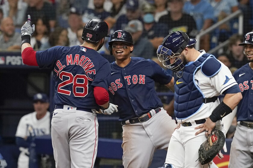 Boston Red Sox's J.D. Martinez (28) is greeted at home plate by Rafael Devers, center, after Martinez hit a three-run home run during the fifth inning, as Tampa Bay Rays catcher Mike Zunino, right, looks down during Game 2 of a baseball American League Division Series, Friday, Oct. 8, 2021, in St. Petersburg, Fla. (AP Photo/Steve Helber)