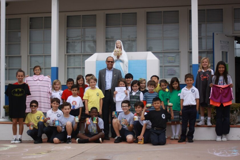 Stella Maris Academy first and third graders pose with the cans of food and clothing they collected during their study of the Corporal Works of Mercy.