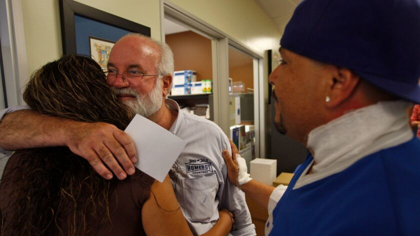 Father Gregory Boyle hugs Nancy Delgadillo while David Minjarez looks on at Homeboy Industries headquarters in Los Angeles on September 14, 2010.