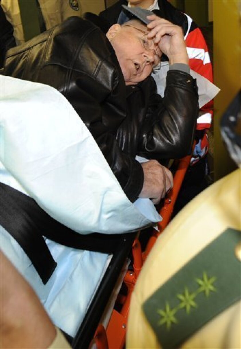 Police officers and medical assistants escort defendant John Demjanjuk, lying on a stretcher, during a trial break in the country court in Munich, southern Germany, on Monday, Nov. 30, 2009. Demjanjuk was brought by ambulance to a Munich court on Monday to face charges of being an accessory to the