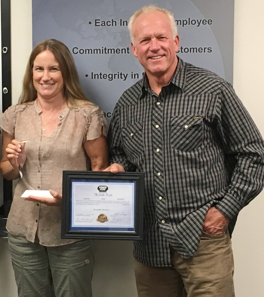 Ramona resident Michelle Scott accepts a 30-year employee award from Power Plus Owner Steve Bray before her bicycle injury.