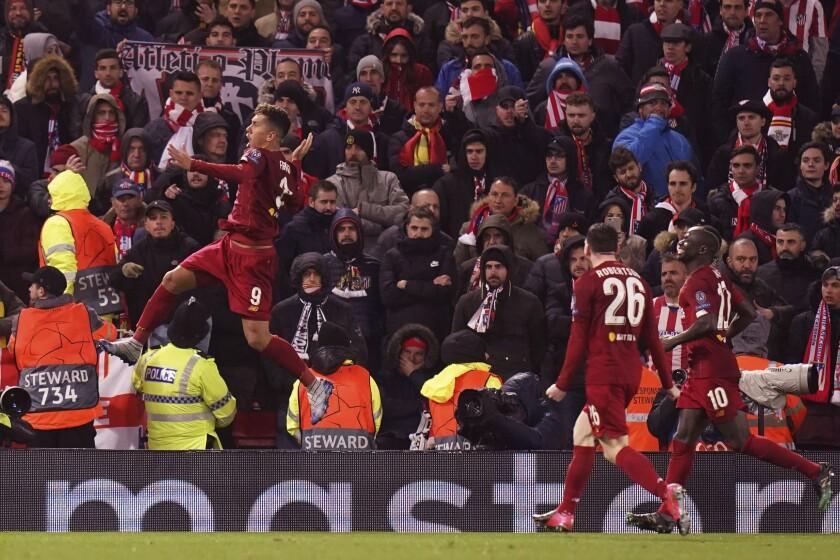 ARCHIVO - En imagen de archivo del 11 de marzo de 2020, el delantero brasileño Roberto Firmino, izquierda, festeja tras anotar el segundo gol del club Liverpool durante un duelo de la Liga de Campeones frente al Atlético de Madrid, en el estadio Anfield de Liverpool, Inglaterra. (AP Foto/Jon Super)